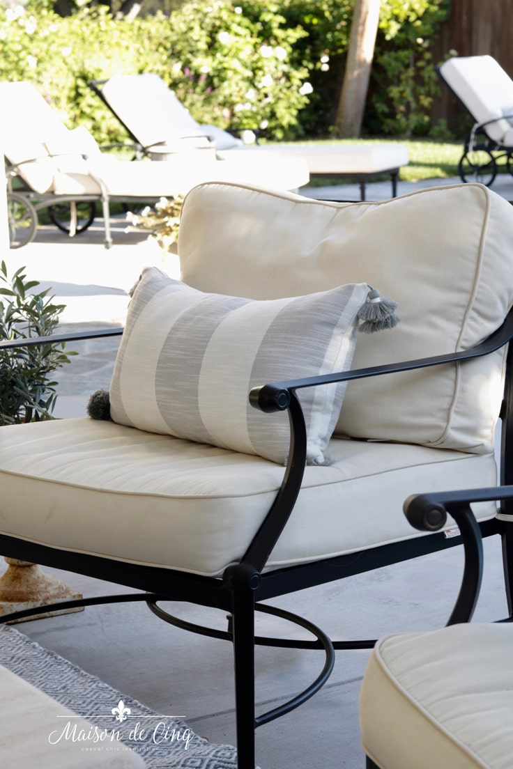 grey and white outdoor pillows on patio chair French country style