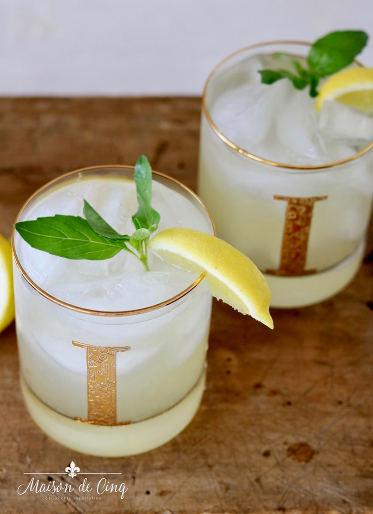 basil vodka gimlet with sprigs of basil and lemon wedges summer cocktail idea
