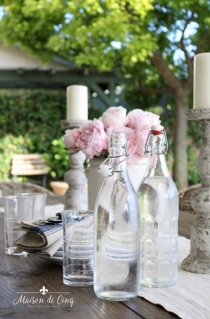 water bottles on outdoor table with flowers summer entertaining ideas