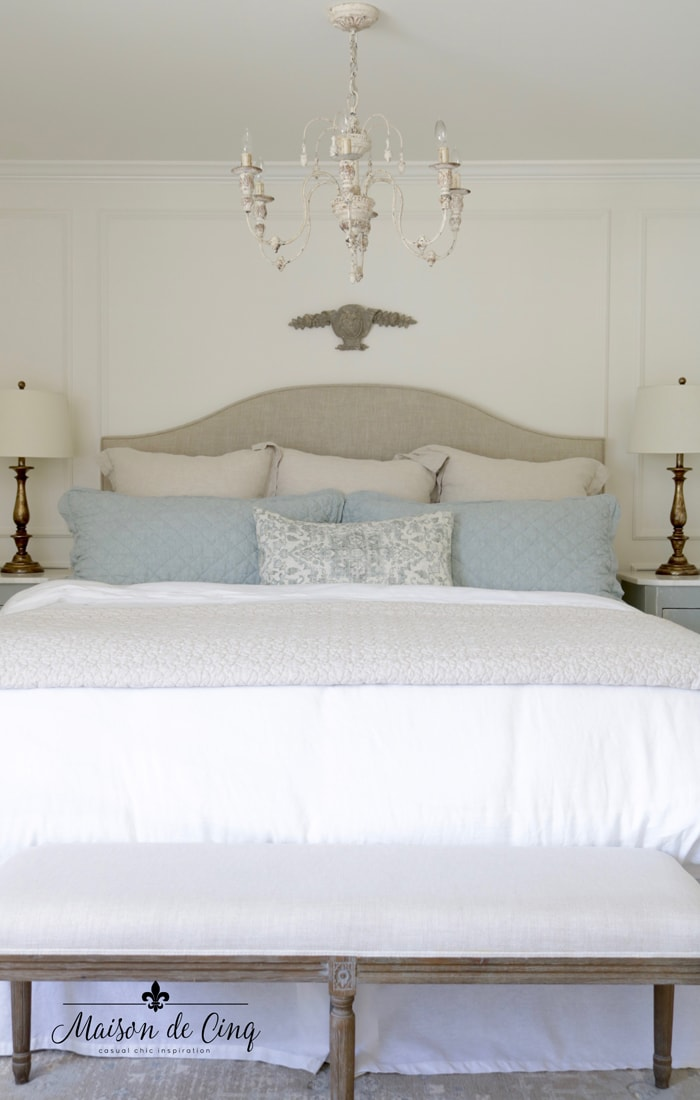 French chandelier neutral linens and blue pillows create a serene master bedroom