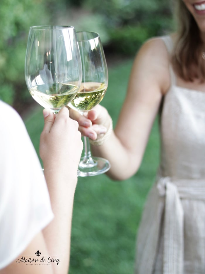 toasting with white wine in backyard summer entertaining
