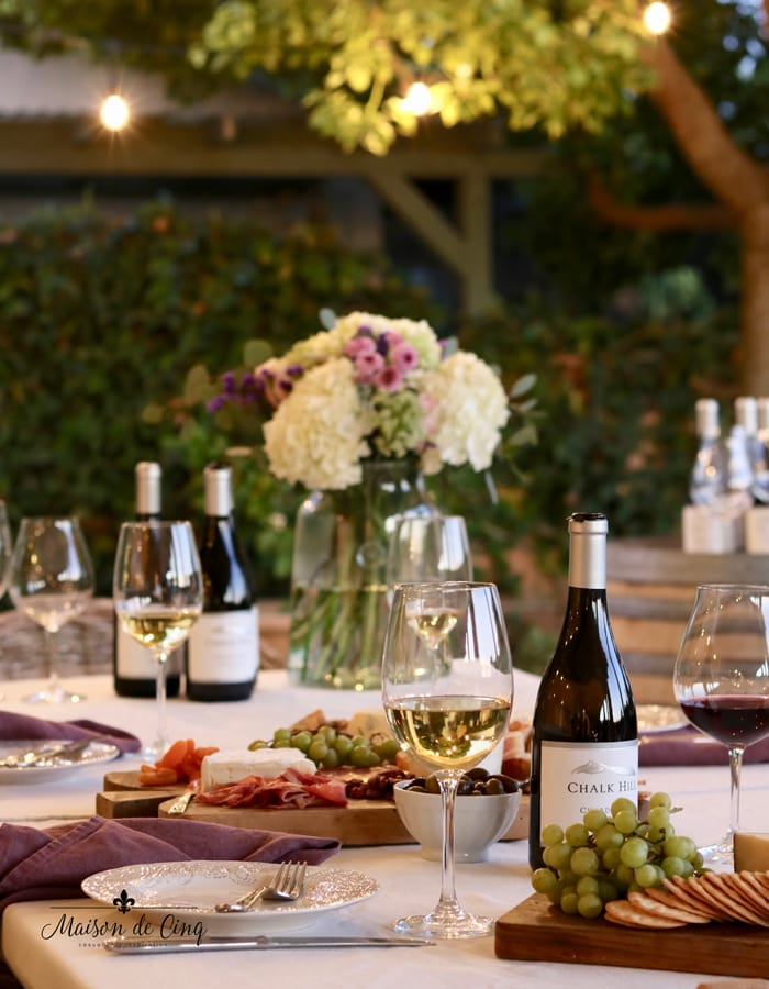 gorgeous summer evening party on the patio white string lights wine and cheese party