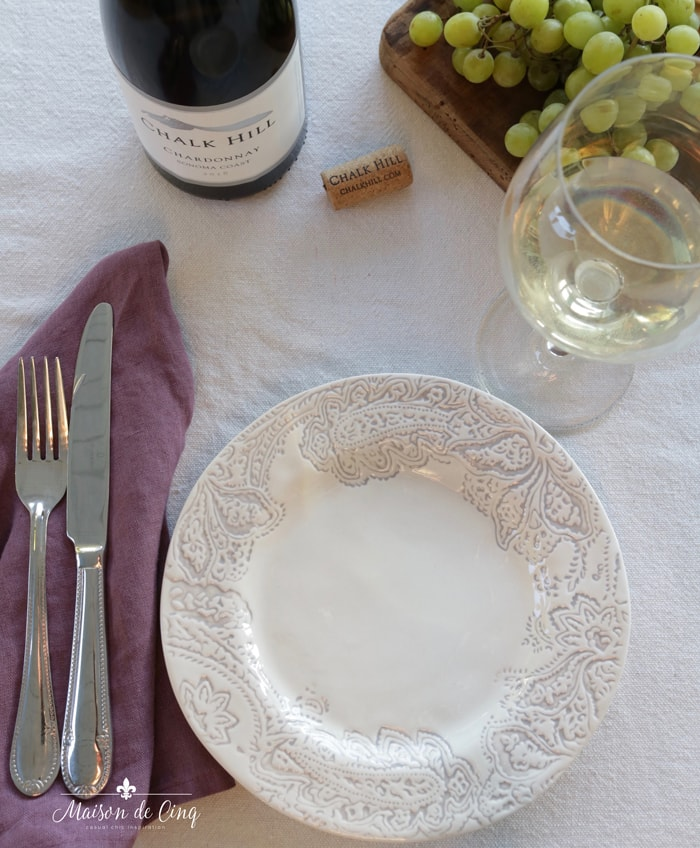 place setting with patterned plate and plum linen napkin