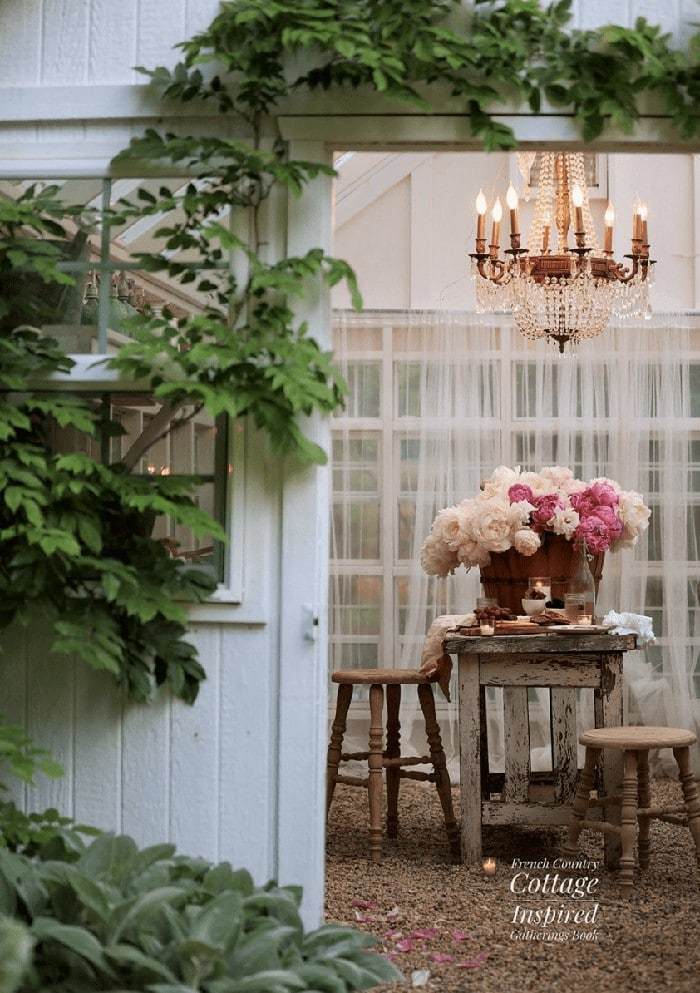 entertaining idea table set in barn with gorgeous peonies and crystal chandelier