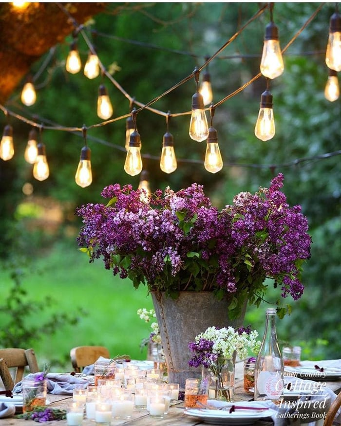 lilacs on table with string lights romantic table setting idea