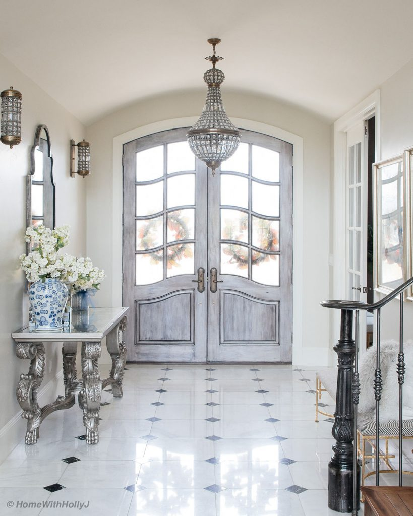 entry way marble floors French country doors crystal chandelier