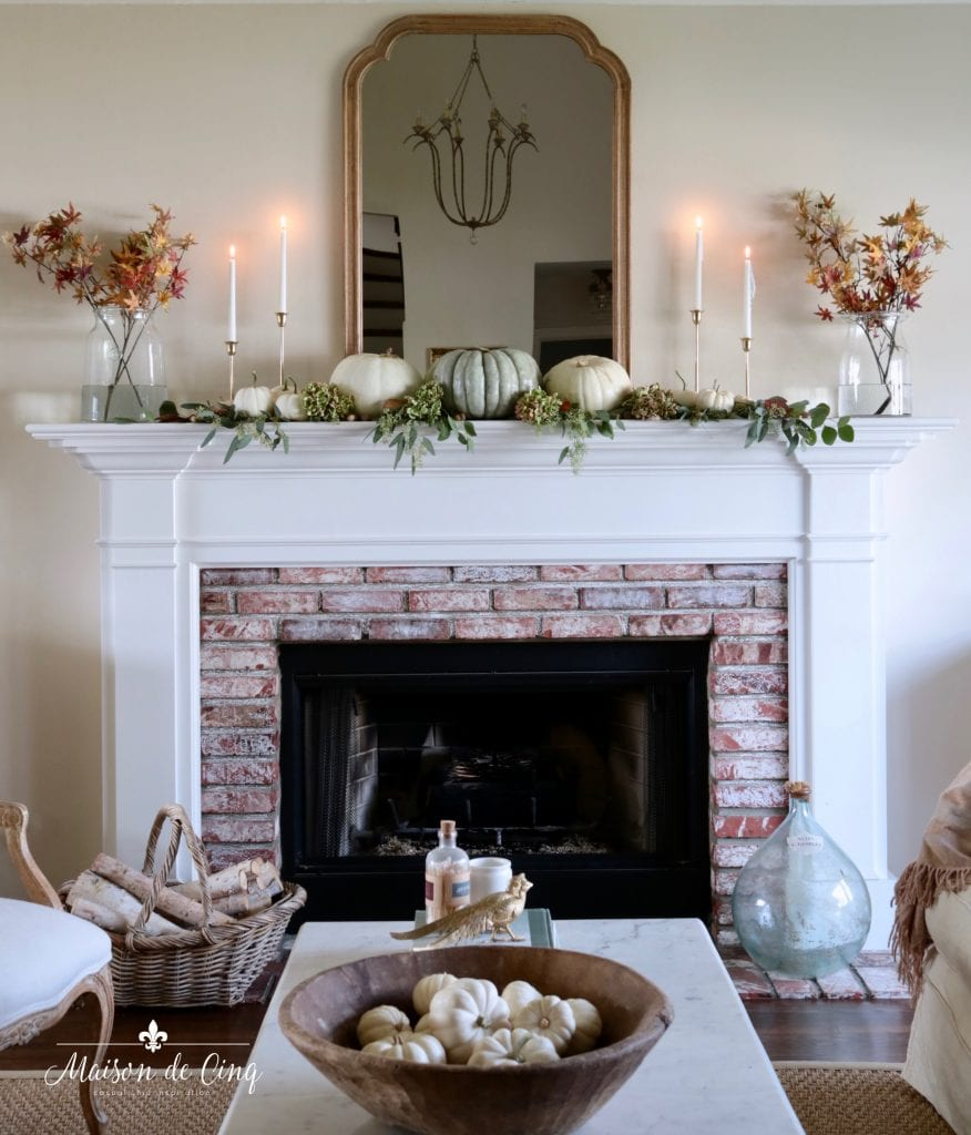 French country living room fall mantel decor with mirrors pumpkins and leaves