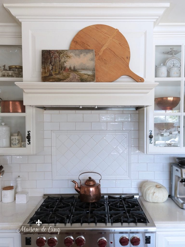 breadboards and vintage art on stove mantel in white French farmhouse kitchen