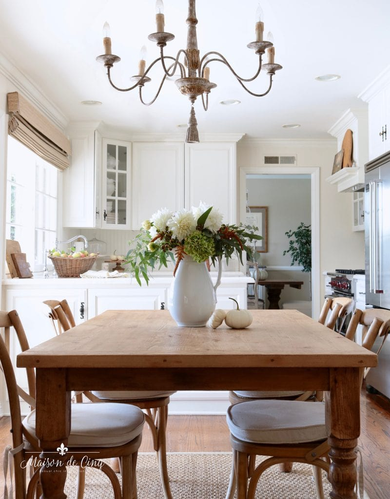 gorgeous French country kitchen with farmhouse table chandelier and fall flowers autumn decorating