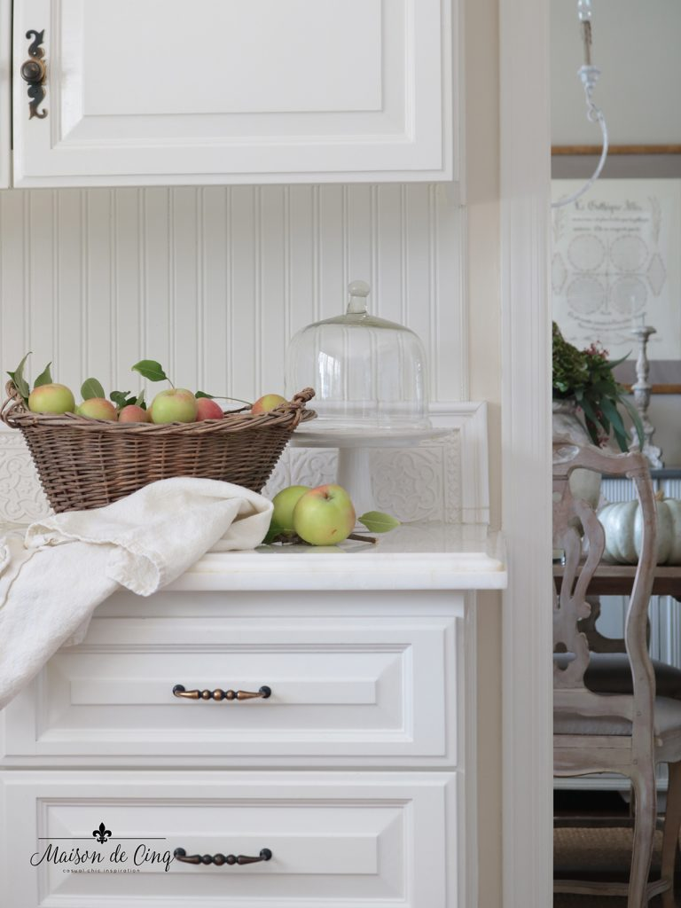 fall decorating ideas in white farmhouse kitchen apples in vintage basket and cake stand