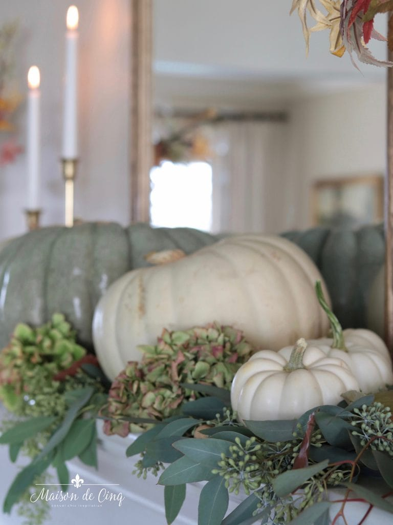 soft and romantic fall mantel with hydrangeas and white and green pumpkins