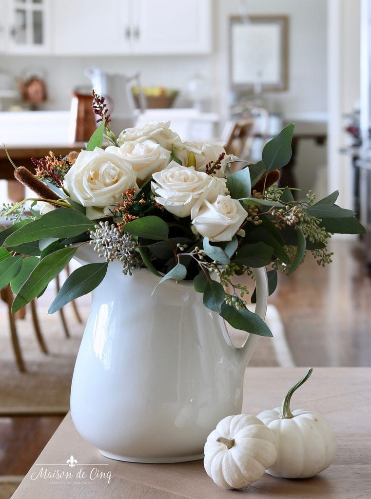 white roses with eucalyptus and white pumpkins pretty fall decorating idea in farmhouse kitchen