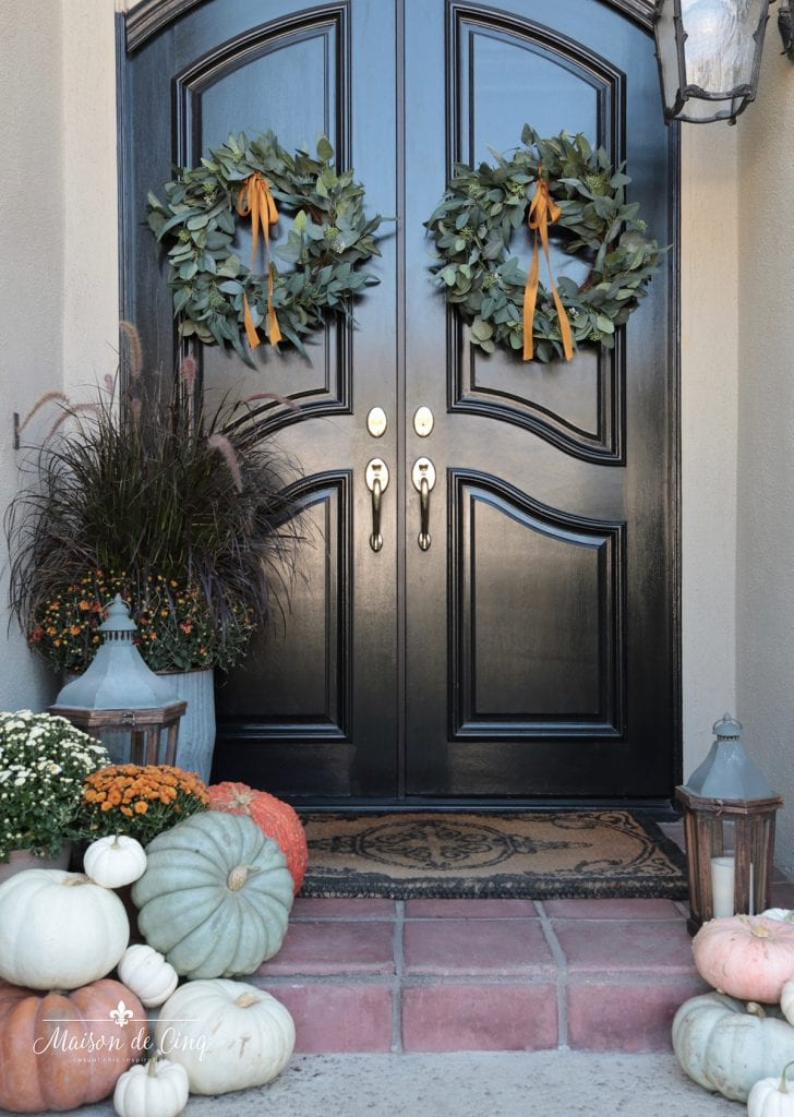 french country style fall porch decor with wreaths mums and pumpkins