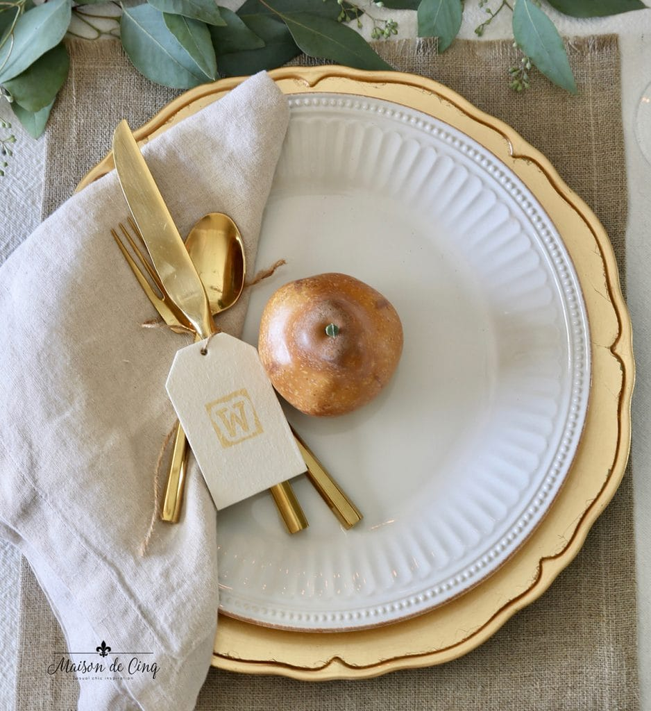 gorgeous fall or Thanksgiving table setting with gold flatware and chargers white plates