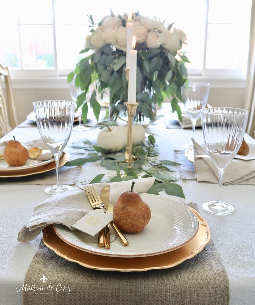 gorgeous neutral Thanksgiving table with gold chargers brass candlesticks and pears and pumpkins