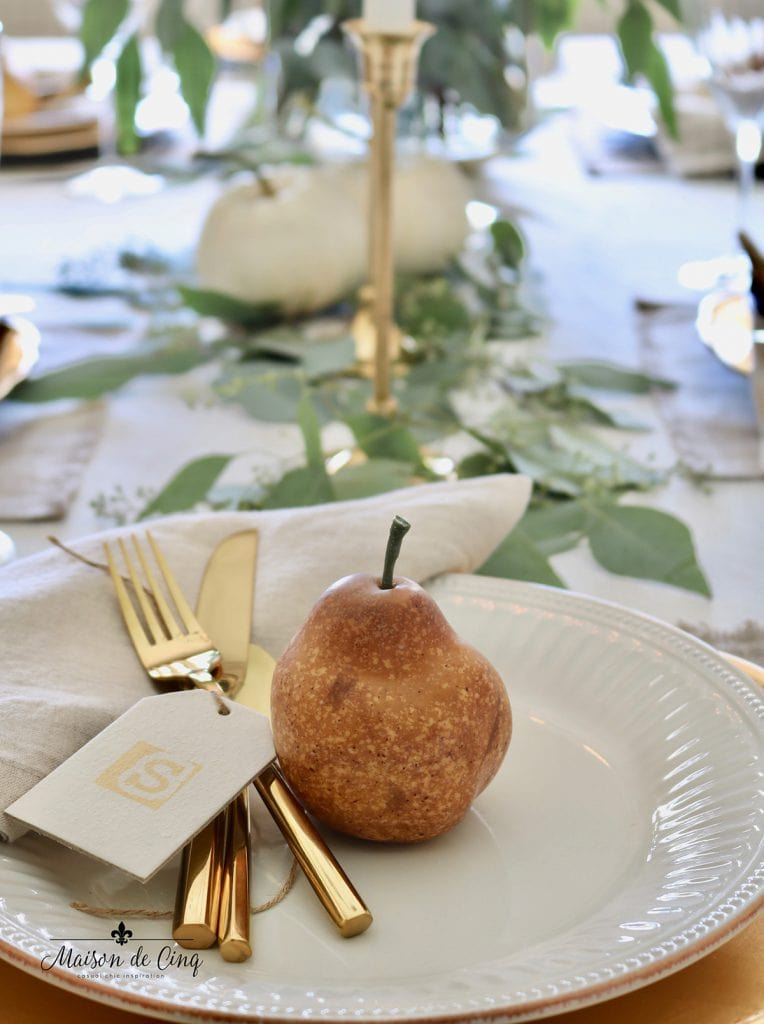 pear and place card with gold flatware on white plate fall table