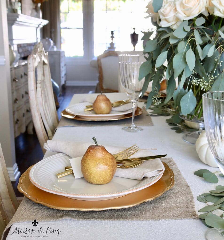 neutral Thanksgiving or fall tablescape idea roses gold chargers and pears