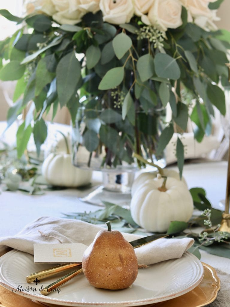 pear on white plate with gold flatware and white roses fall table setting idea