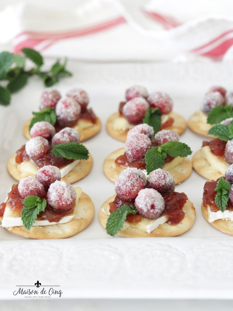 sparkling cranberry and brie bites with mint sprigs on white plate