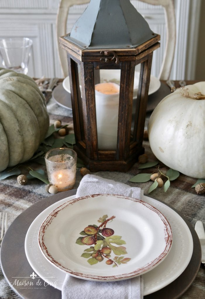 warm and cozy fall table setting with lantern pretty plates plaid tablecloth and pumpkins