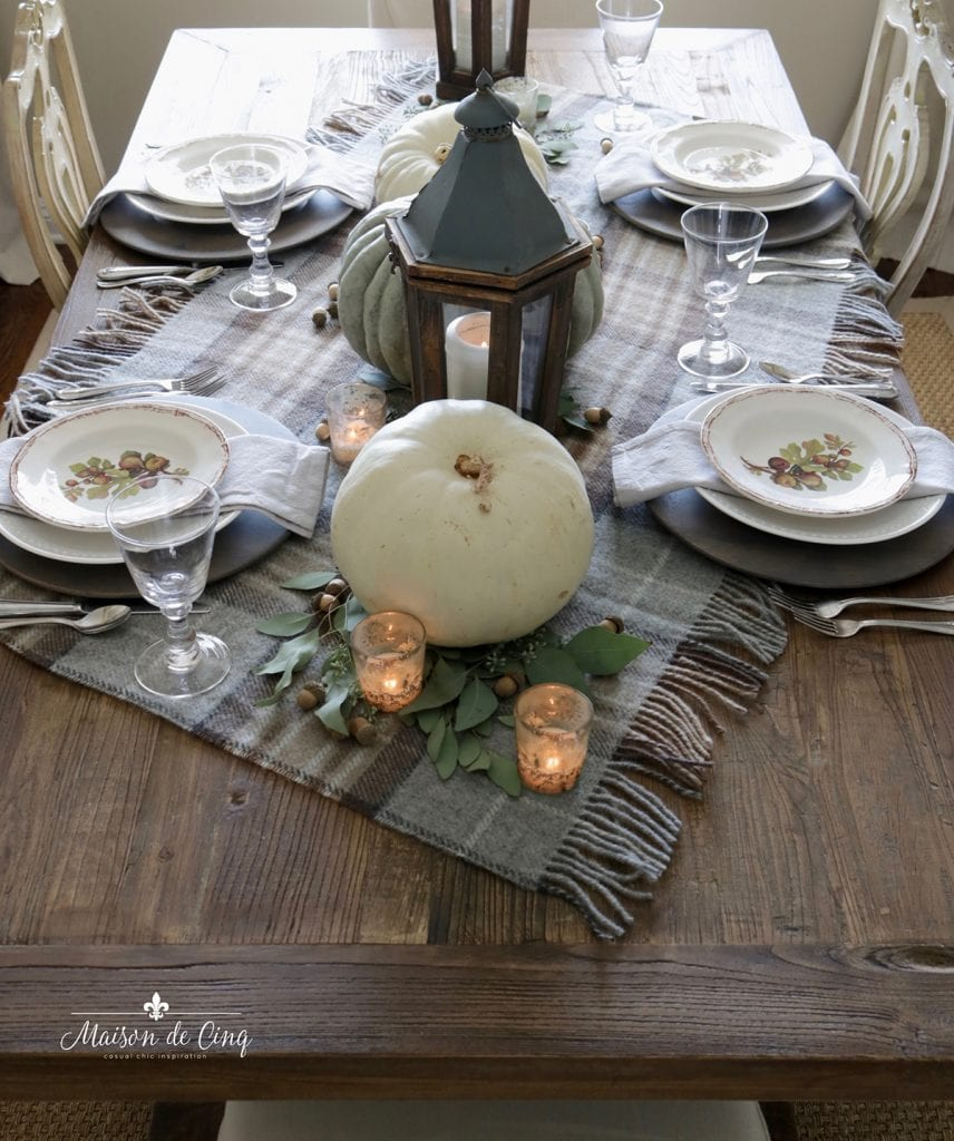 warm and cozy fall table setting plaid tablecloth lanterns and neutral pumpkins