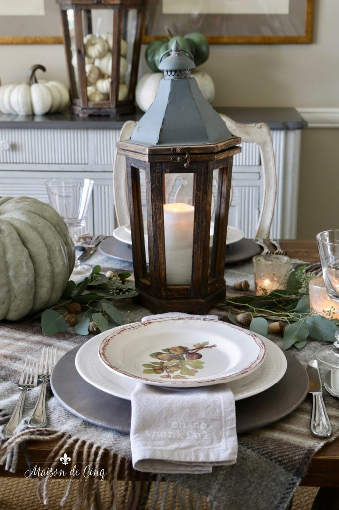 cozy fall thanksgiving table setting with plaid pumpkins and greenery