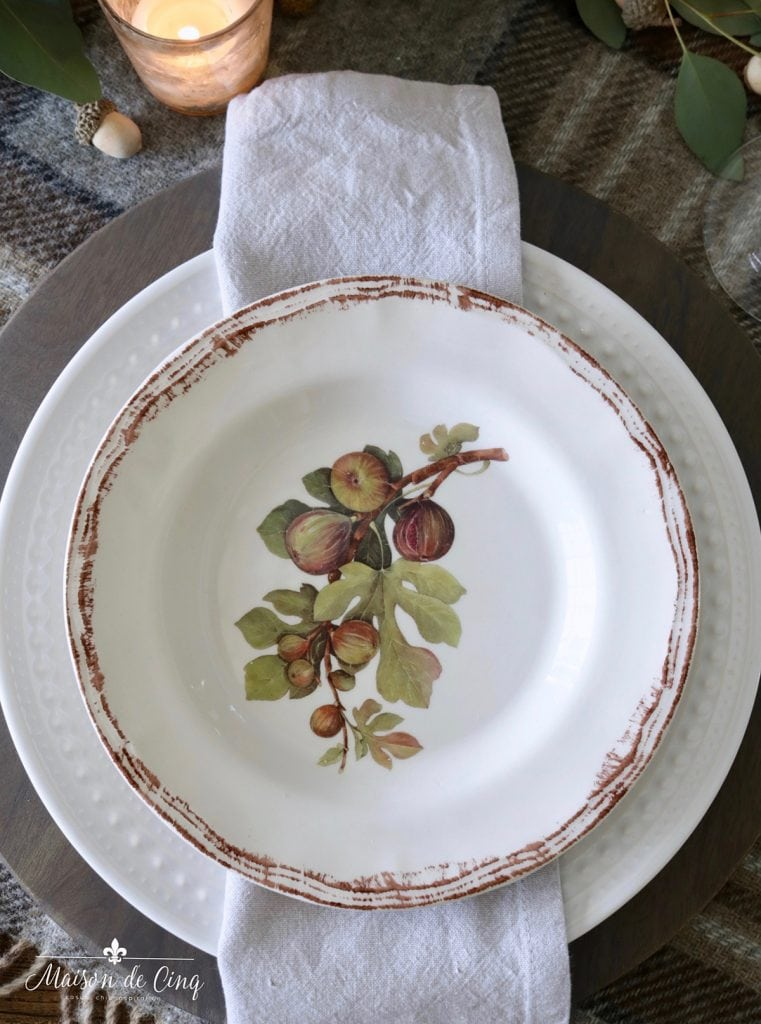 fig plates layered over white dinner plate and wood charger fall tablescape idea