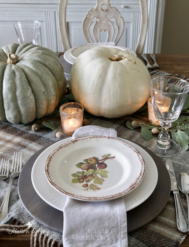 neutral pumpkins plaid tablecloth and greenery Thanksgiving table idea