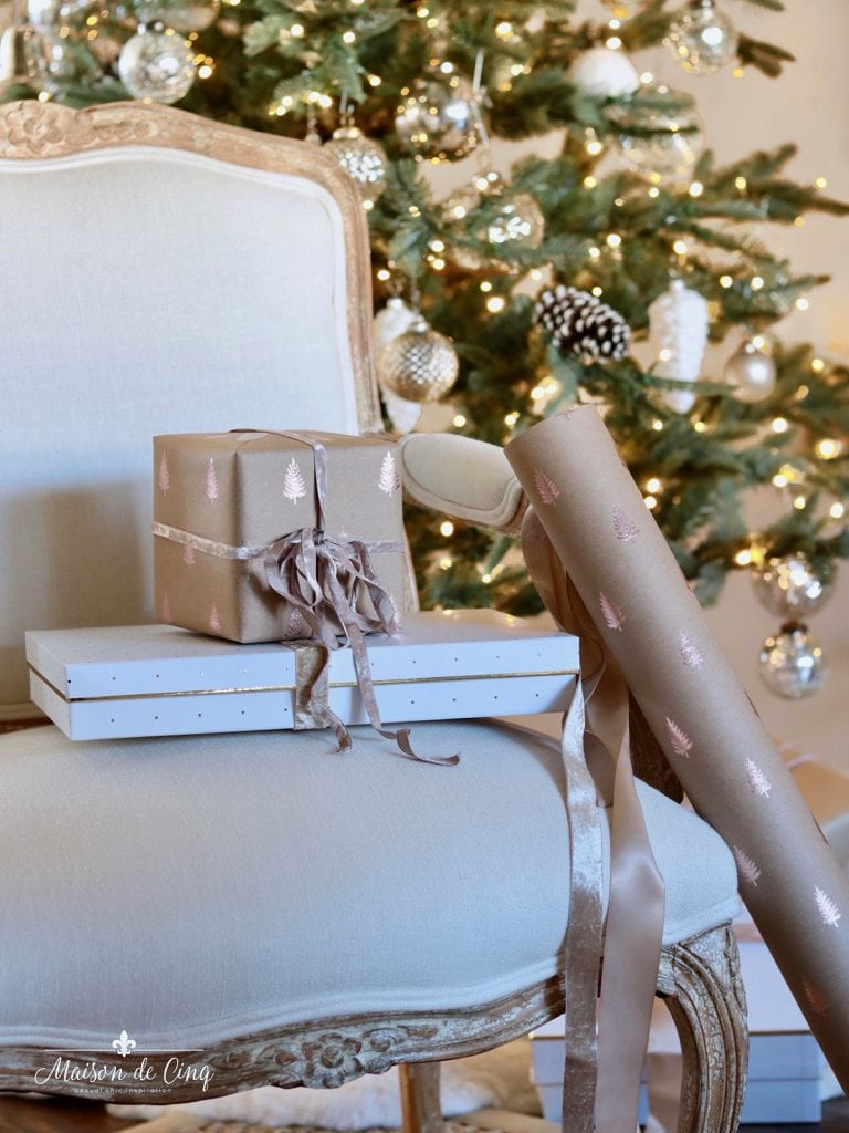 French chair with presents wrapping paper and ribbon by Christmas tree
