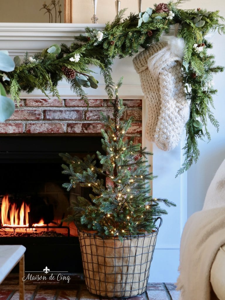 tabletop tree in wire basket garland stockings candles on mantel