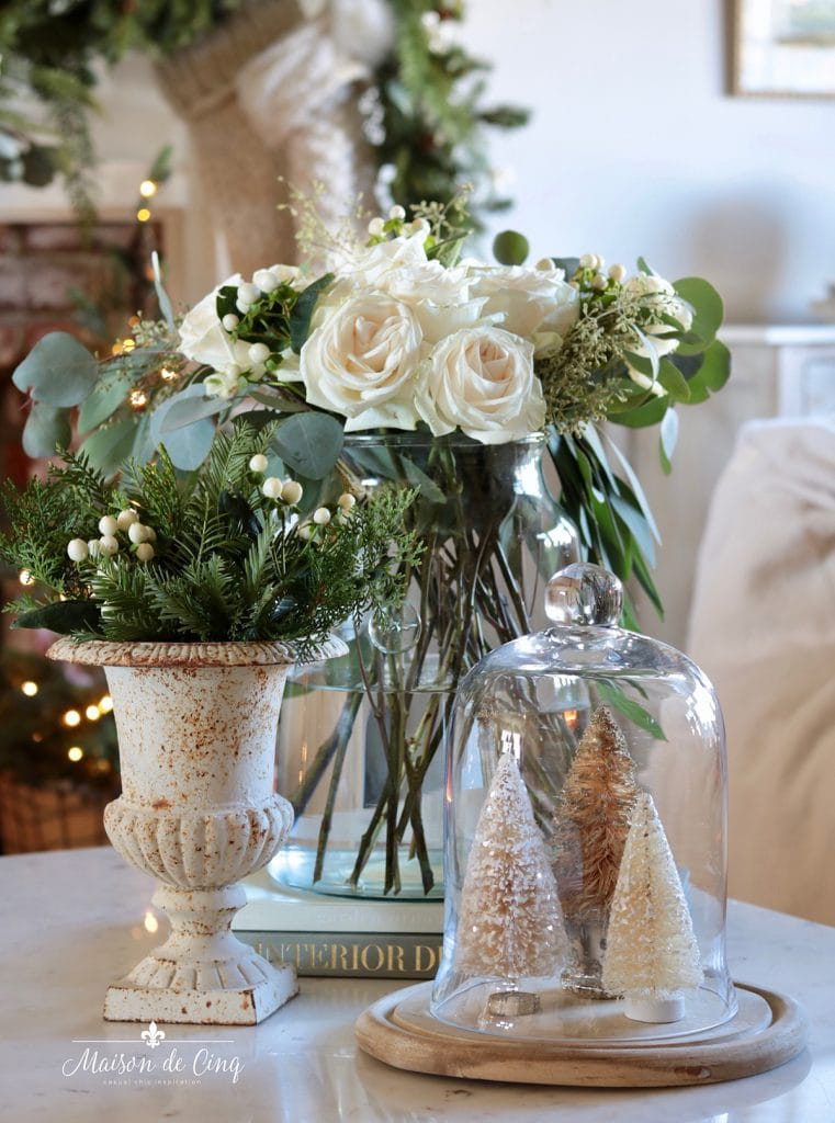 gorgeous French country Christmas vignette white roses greenery in urn and bottle brush trees