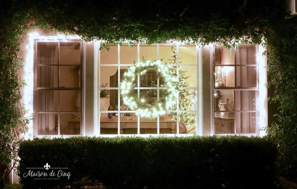 outdoor Christmas decor lit wreath and garland in window