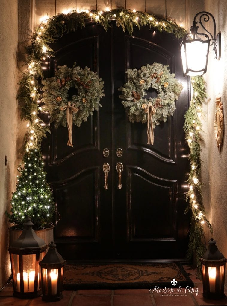 front door porch Christmas holiday decor lit garland wreaths and lanterns