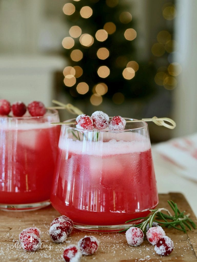 gorgeous shot of cranberry whiskey sour cocktail with sugared cranberries and rosemary garnish