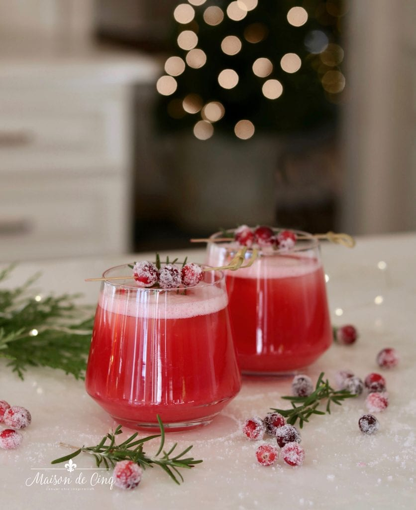 cranberry whiskey sour two glasses with sugared cranberries and rosemary garnish