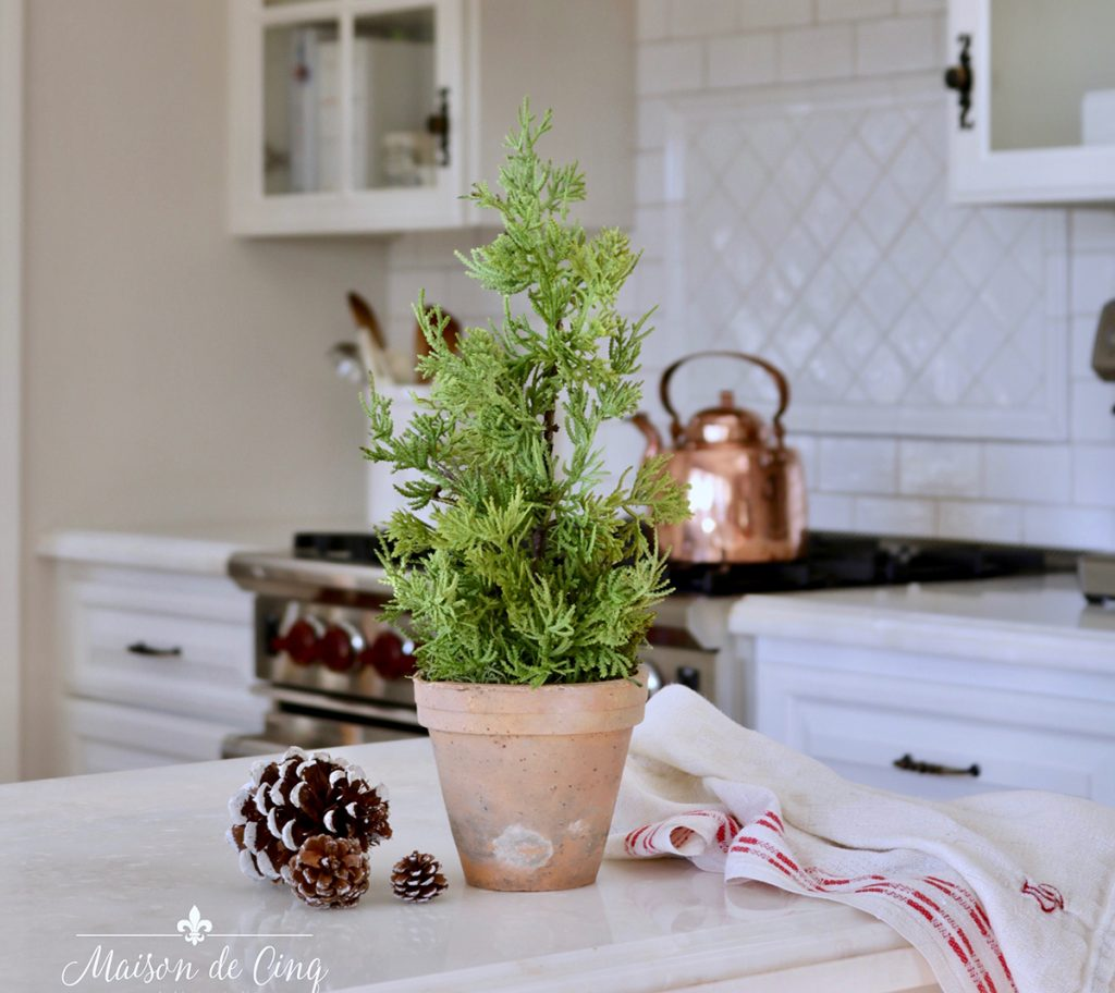 gorgeous kitchen Christmas decor little pine tree on counter with pine cones
