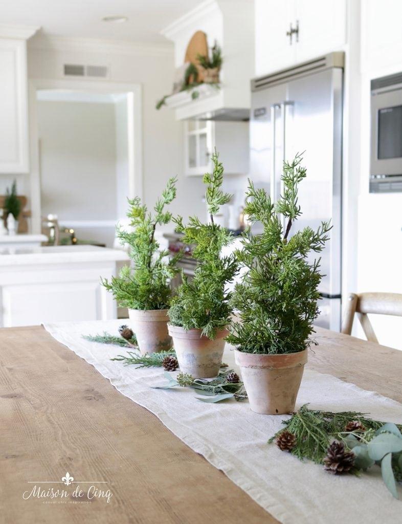 trio of little pine trees on farmhouse table beautiful European Christmas decor ideas