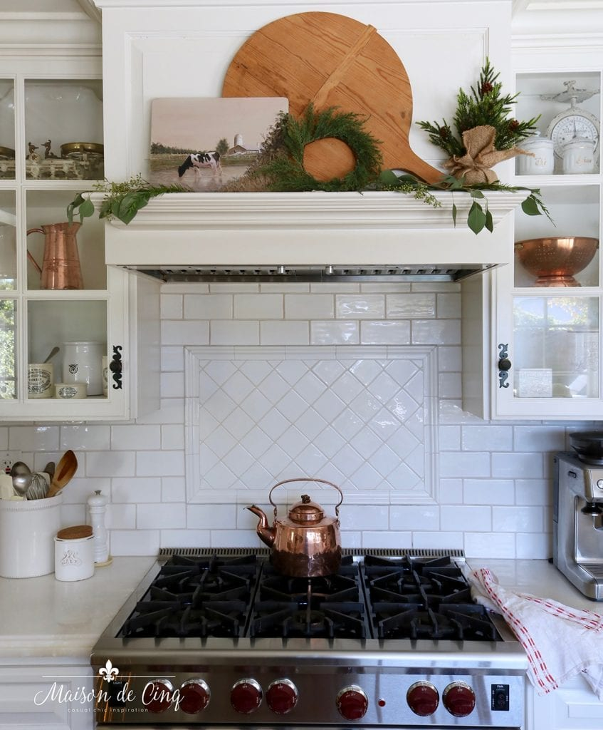 Christmas kitchen stove mantel with greenery tiny pine tree bread board and wreath