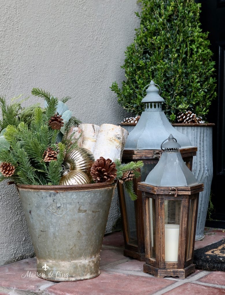 porch decorating ideas bucket with greens and logs and rustic lanterns
