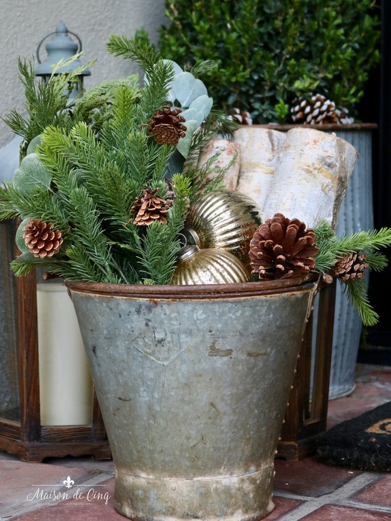 rustic vintage bucket with greens, pinecones and logs holiday porch decor
