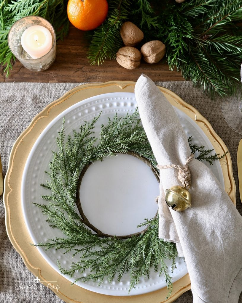 mini wreath on white plate over gold charger holiday tablescape