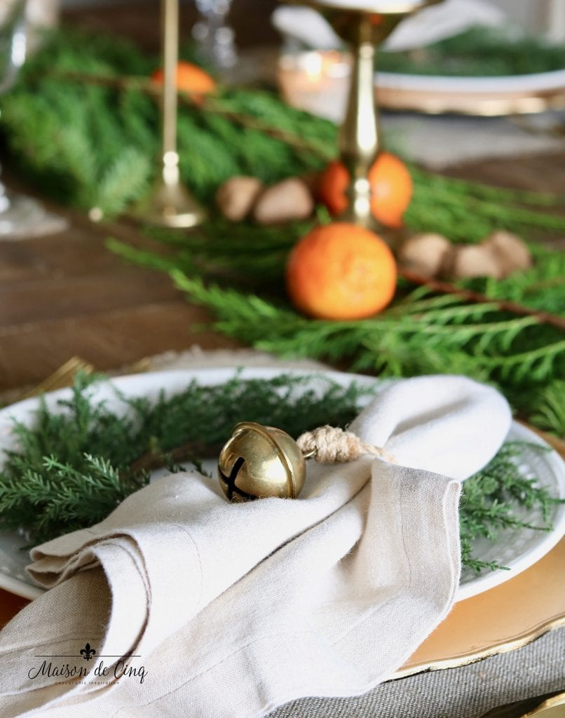 brass bell on linen napkin holiday tablescape ideas