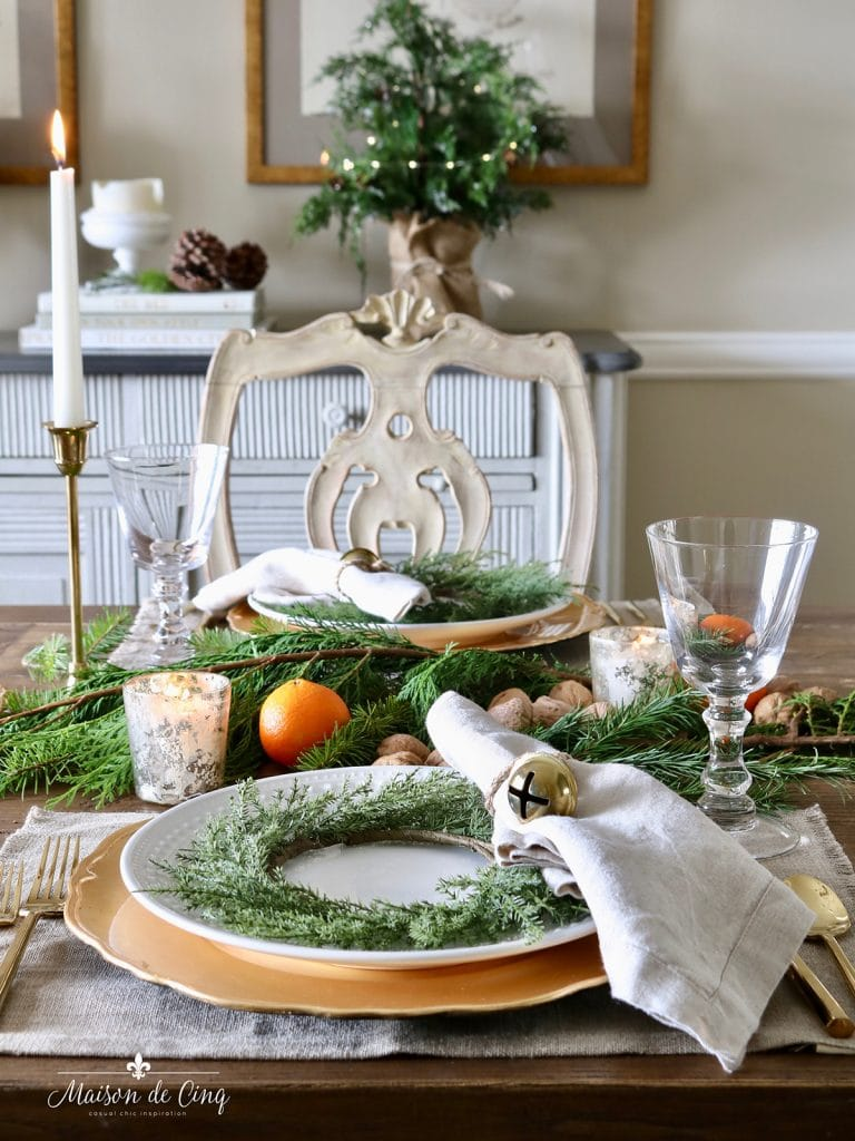 gorgeous European style holiday table setting with oranges and gold chargers
