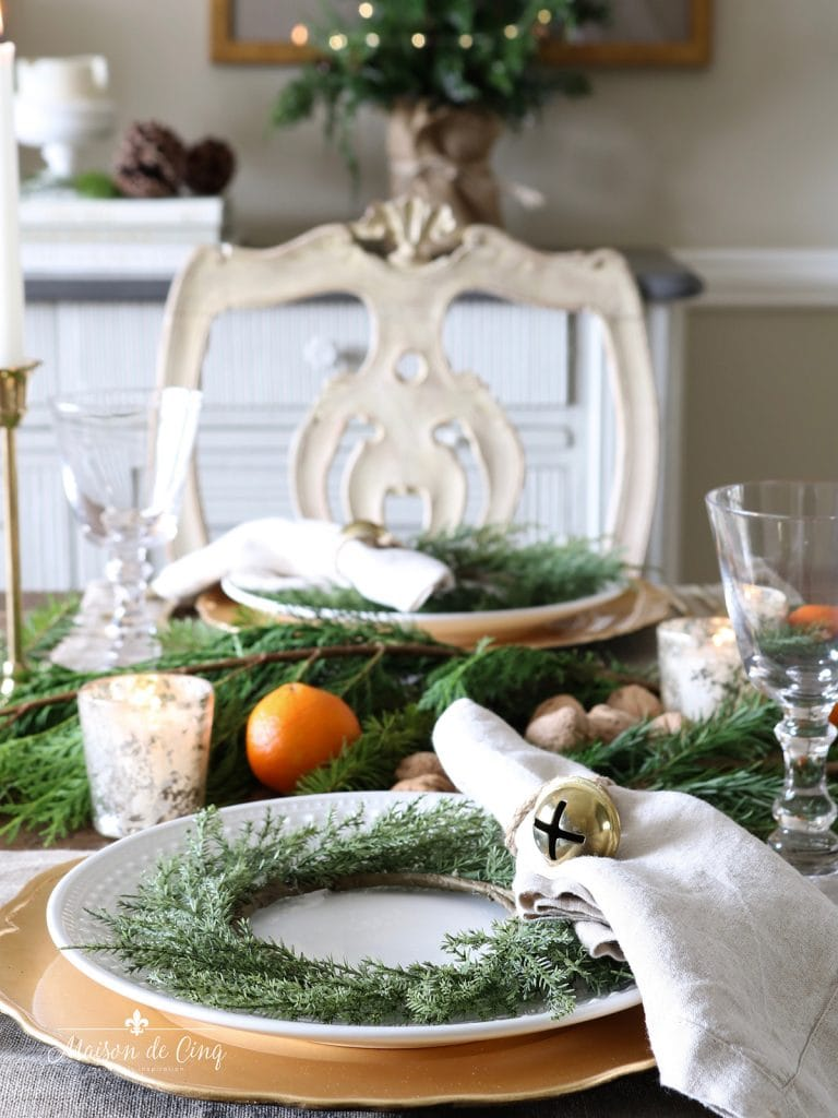 gorgeous holiday Christmas tablescape with greenery oranges and mercury glass votives