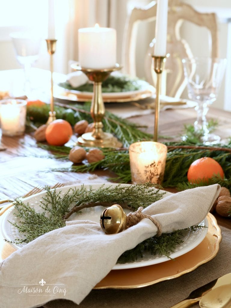 cozy holiday tablescape greens oranges walnuts and brass candles centerpiece