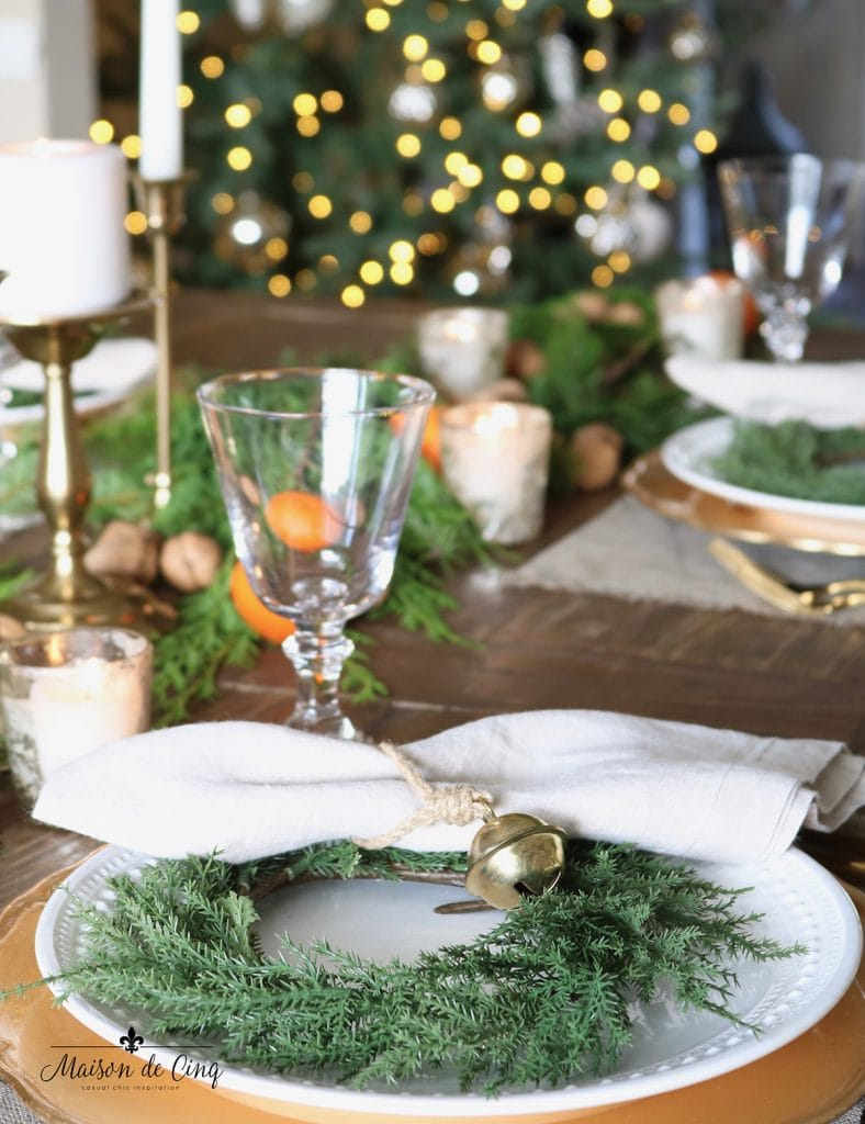 little wreath on white plate with bell napkin ring Christmas table setting ideas