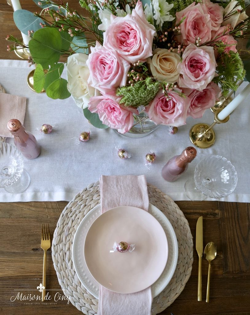 gorgeous pink roses overhead romantic Valentine's day table setting with pink and white plates