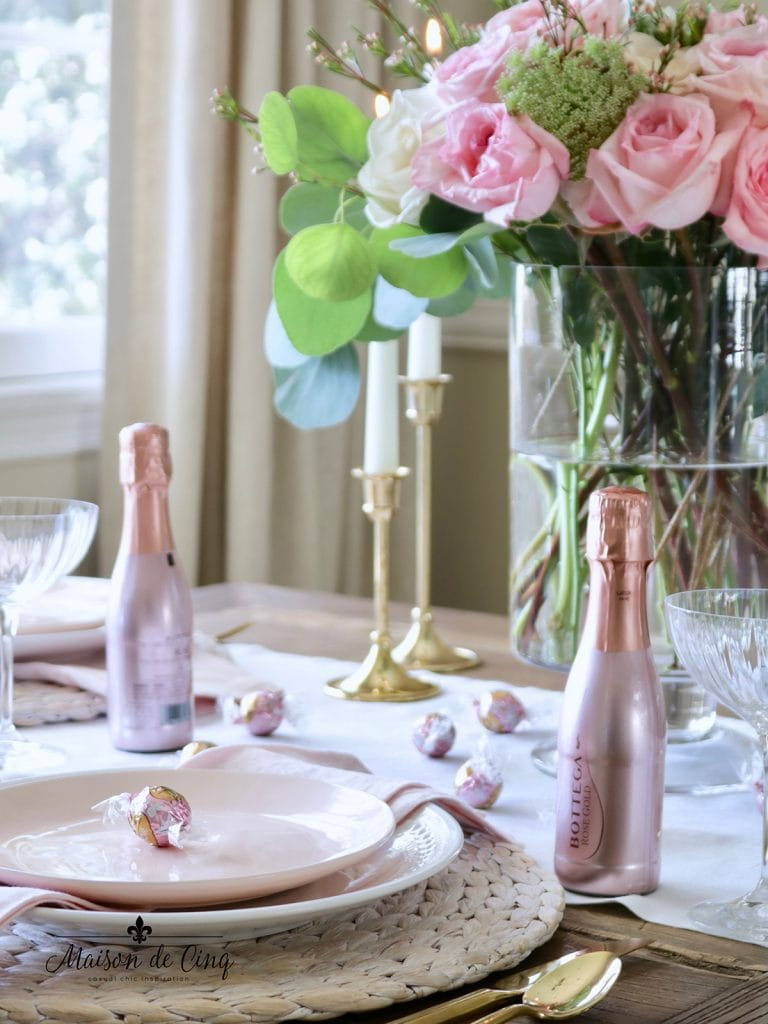 rose bottles and chocolates with pink flowers create a pretty Valentine's day table setting