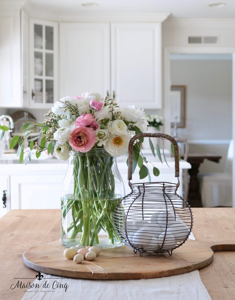gorgeous pink and white ranunculus in glass vase with eggs easter spring decorating in the kitchen