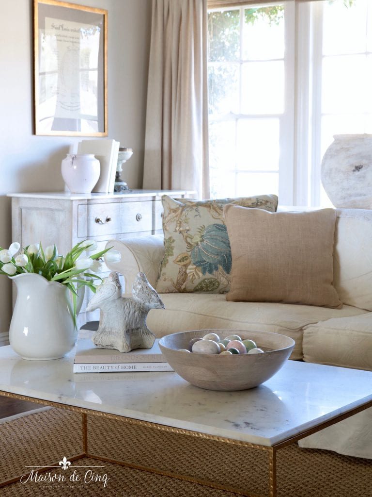 spring living room with blue floral pillows tulips and marble eggs